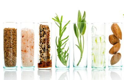 Glasses with different foods in them: lemon, cucmber, seeds, herbs etc.